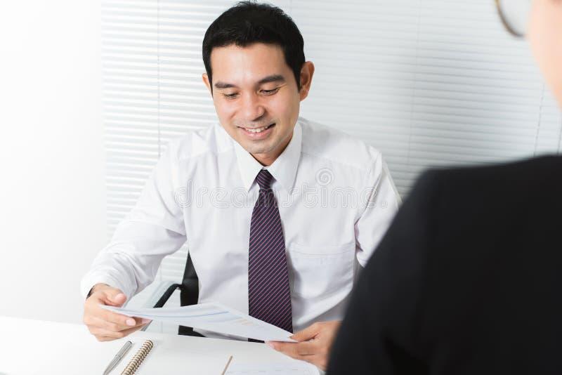 Uśmiechnięty biznesmena czytanie sprawdza dokument przy jego biurkiem w t obraz stock