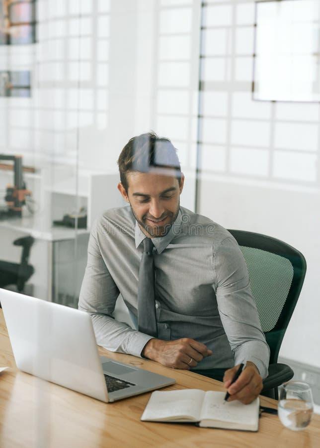 Uśmiechnięty biznesmena obsiadanie przy pracą pisze pomysłach w notatniku obrazy stock