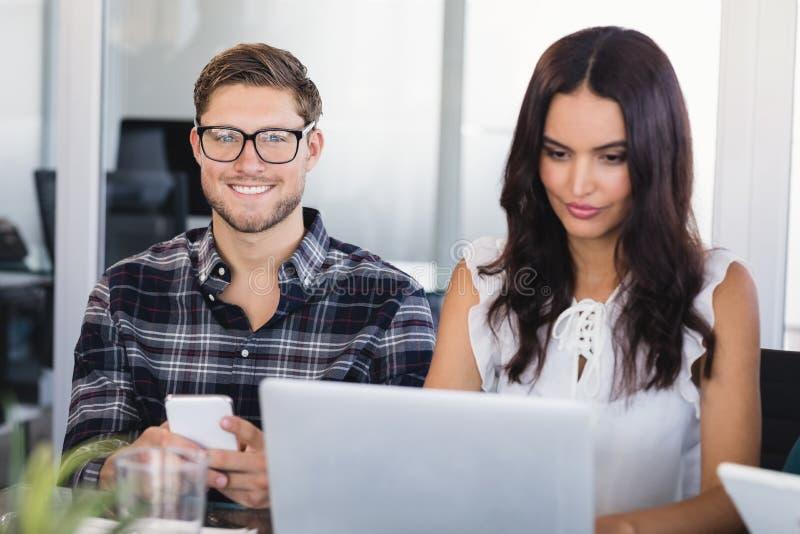 Uśmiechnięty biznesmena obsiadanie z żeńskim kolegą przy biurem fotografia stock
