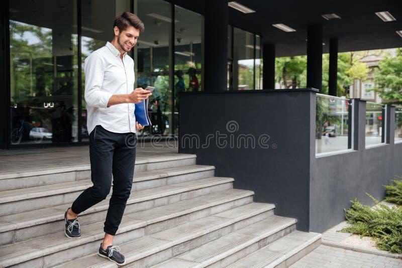 Uśmiechnięty biznesmena odprowadzenie i używać blisko centrum biznesu telefon komórkowy zdjęcia stock