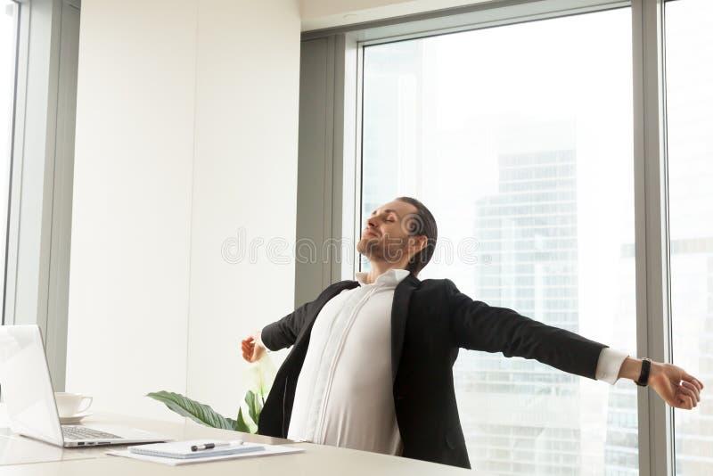 Uśmiechnięty biznesmena rozciąganie przy miejscem pracy w nowożytnym biurze obrazy royalty free