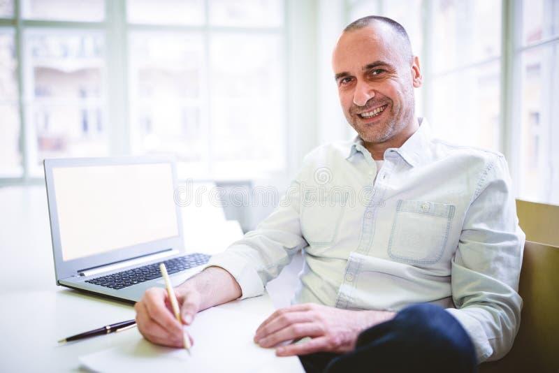Uśmiechnięty biznesmena writing dokument fotografia royalty free