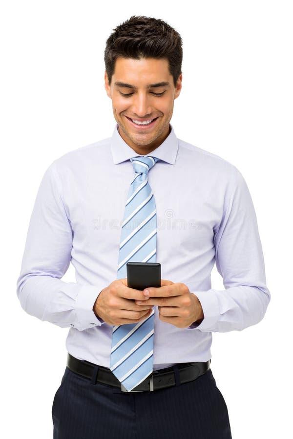 Uśmiechnięty biznesmena wysylanie sms Na Mądrze telefonie zdjęcie stock