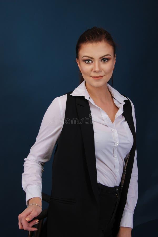 Uśmiechnięty biznesowej kobiety błękitny kostium ubierał pozycję przeciw błękitnemu tłu Portret m?oda kobieta obrazy stock