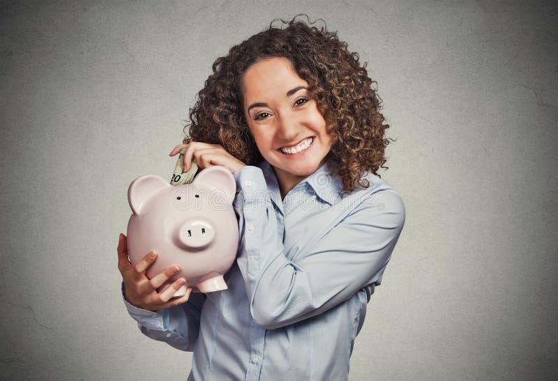 Uśmiechnięty biznesowej kobiety banka pracownik, studencki mienia prosiątka bank fotografia stock