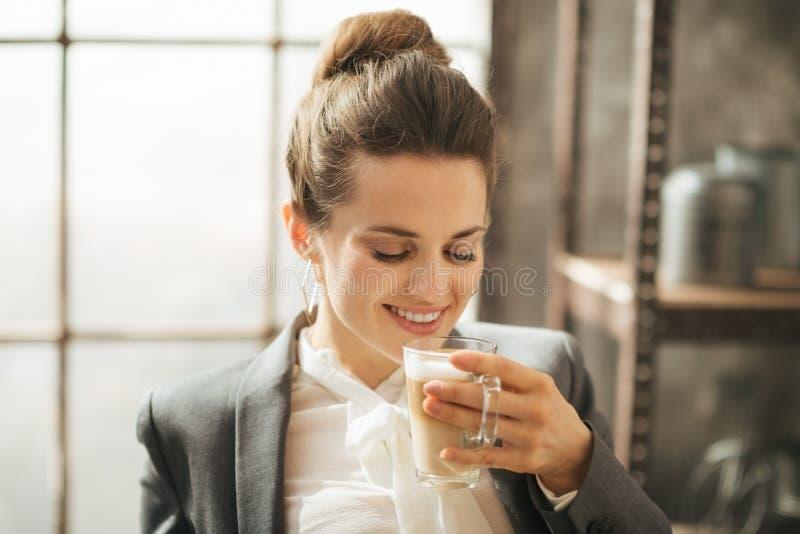 Uśmiechnięty bizneswoman cieszy się filiżanki kawy latte macchiato zdjęcia royalty free