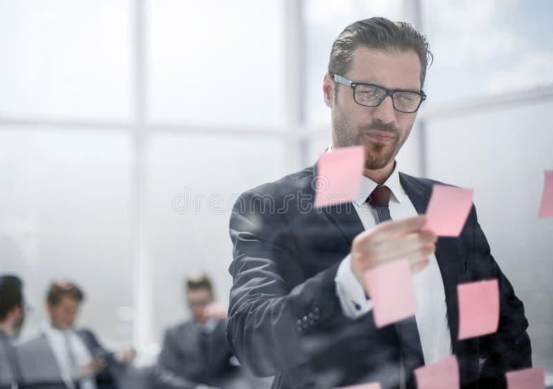 Uśmiechnięty bizneswoman czyta kleiste notatki na szkle zdjęcia stock