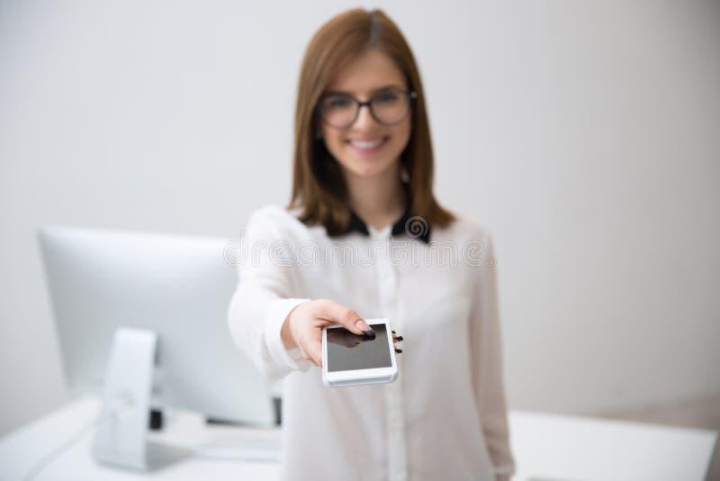uśmiechnięty bizneswoman daje smartphone na kamerze zdjęcie stock
