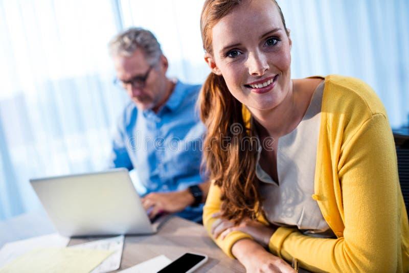 Uśmiechnięty bizneswoman i skoncentrowany biznesmen zdjęcie stock