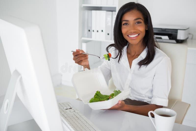 Uśmiechnięty bizneswoman je sałatki przy jej biurkiem fotografia royalty free
