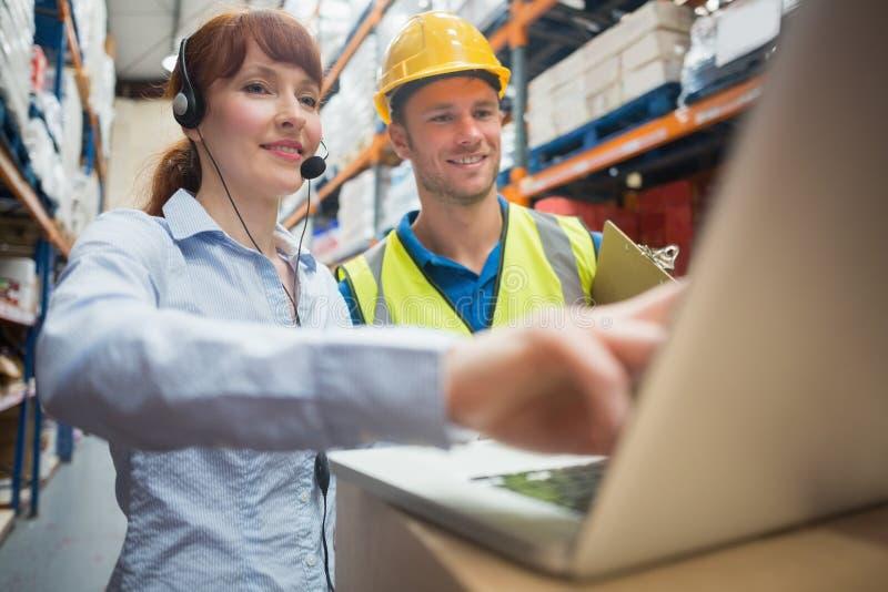 Uśmiechnięty bizneswoman jest ubranym słuchawki używać laptop obraz stock