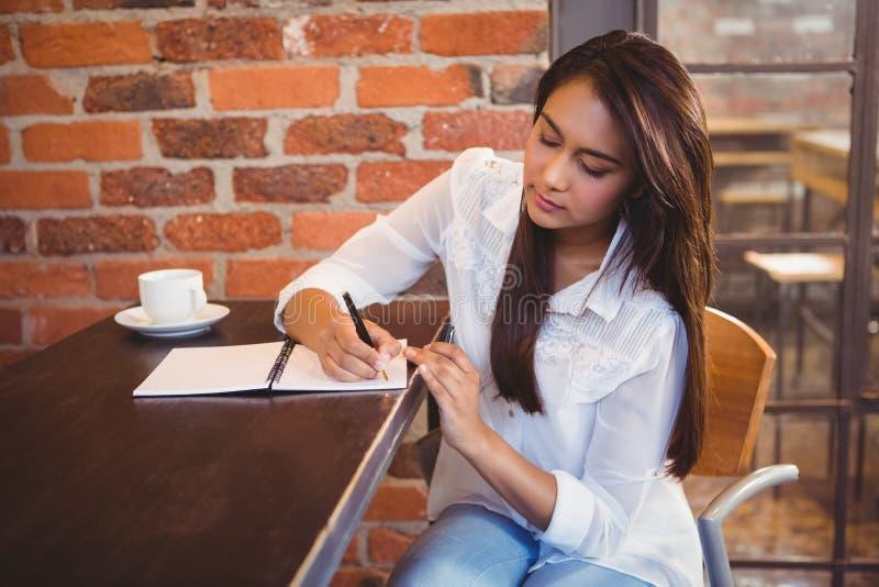 Uśmiechnięty bizneswoman ma kawę i planowanie jej tydzień fotografia stock