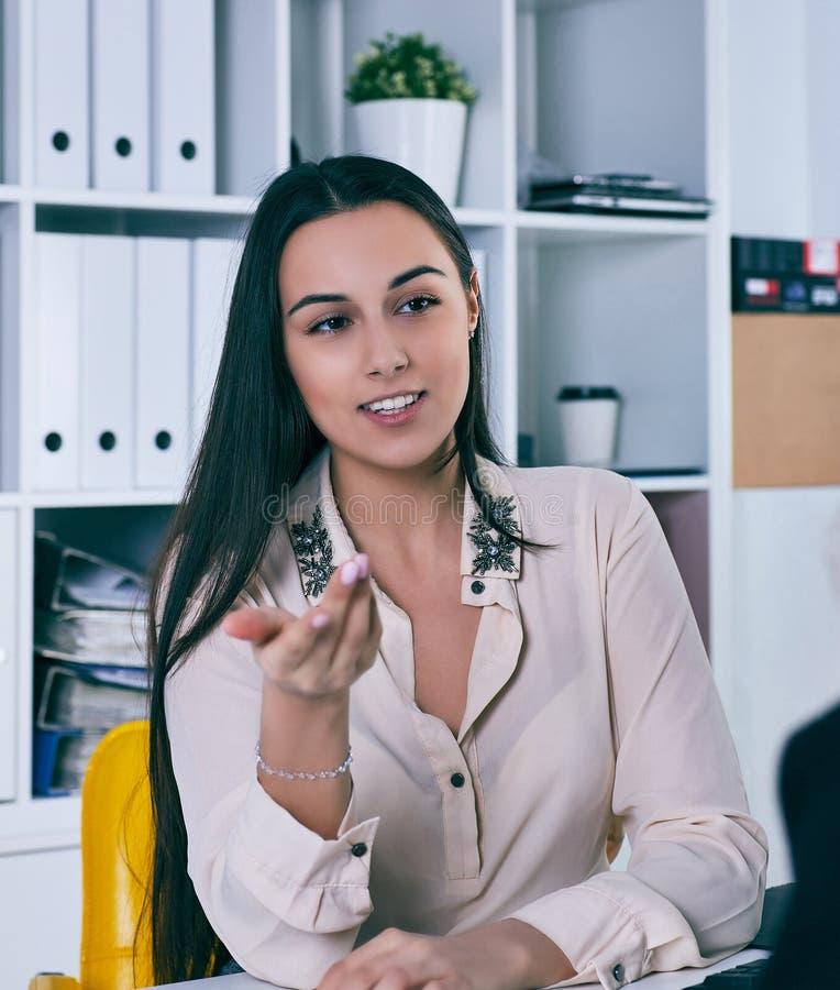 Uśmiechnięty bizneswoman opowiada jej kolega w biurze obraz royalty free