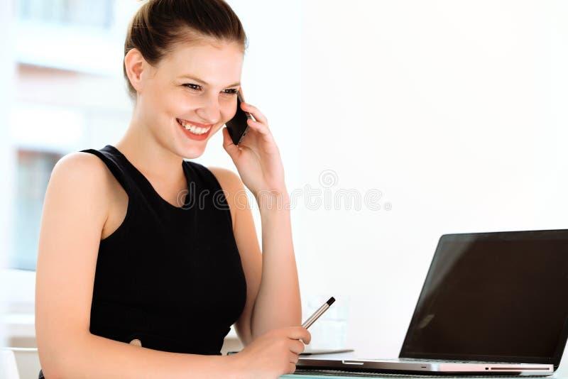 Uśmiechnięty bizneswoman opowiada na telefonie komórkowym w biurze zdjęcia stock
