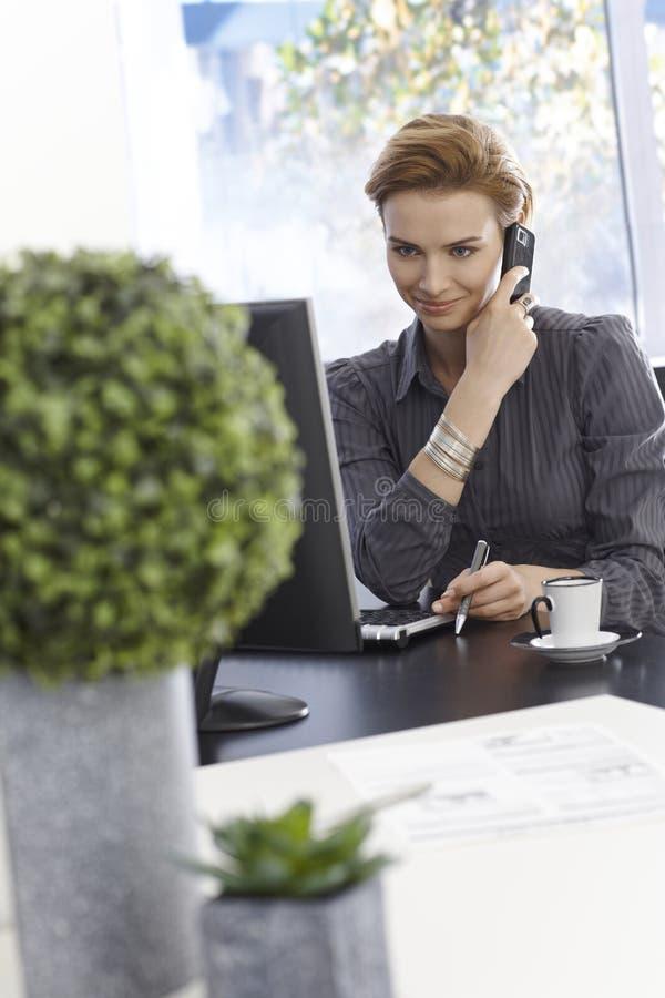 Uśmiechnięty bizneswoman opowiada na wiszącej ozdobie zdjęcie stock