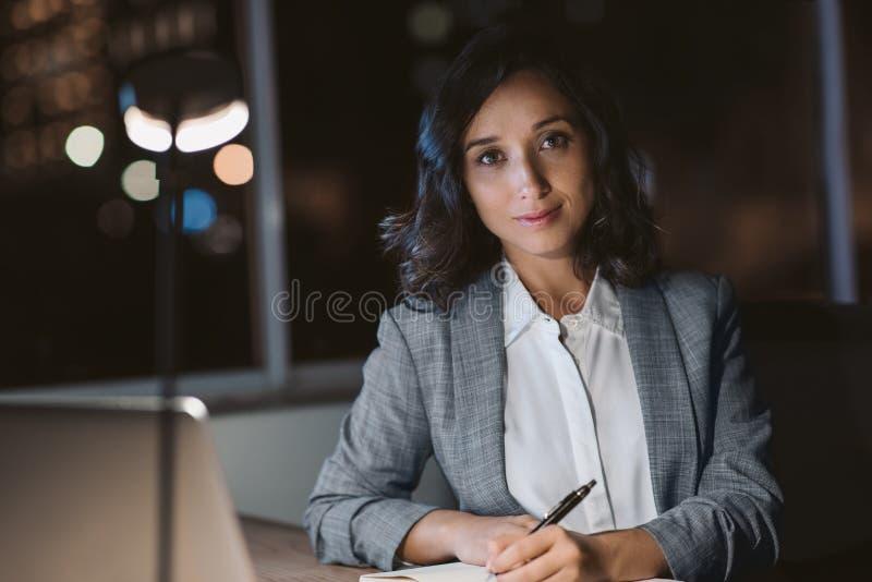 Uśmiechnięty bizneswoman pracuje przy jej biurkiem w ciemnym biurze zdjęcia royalty free