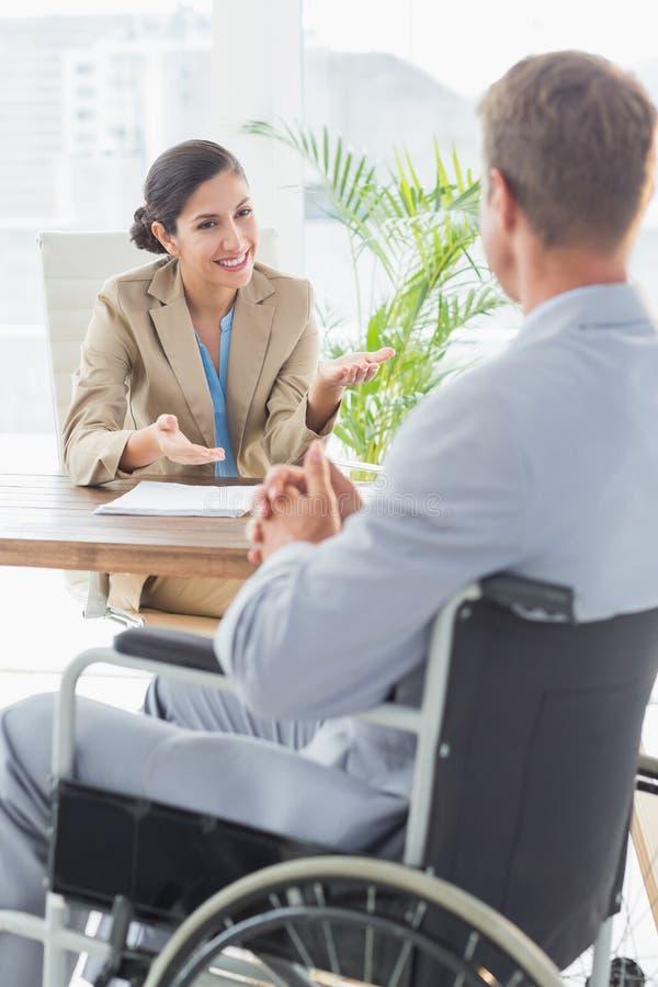 Uśmiechnięty bizneswoman przeprowadza wywiad niepełnosprawnego kandydata zdjęcie stock