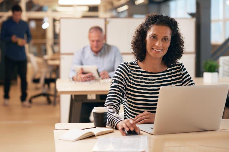 Uśmiechnięty bizneswoman przy pracą w ruchliwie biurze zdjęcia royalty free