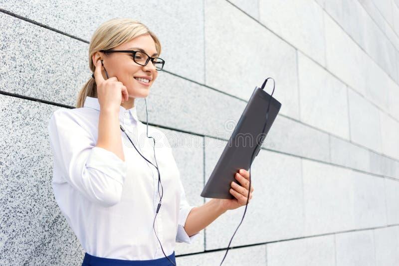 Uśmiechnięty bizneswoman słucha muzyka zdjęcia stock