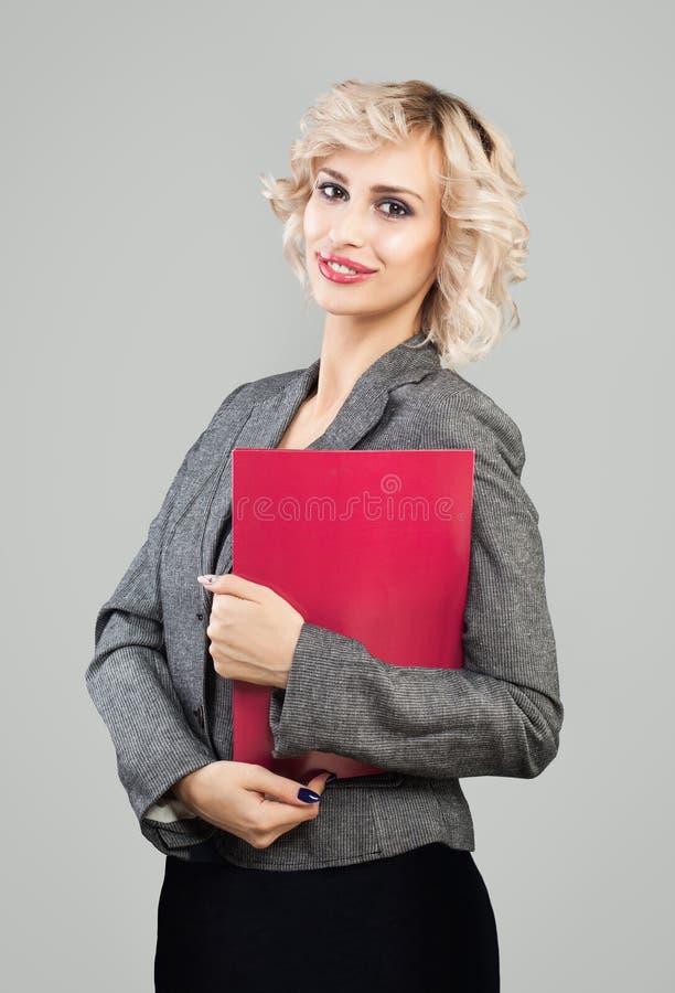 Uśmiechnięty bizneswoman w kostiumu mienia czerwieni falcówce obrazy stock