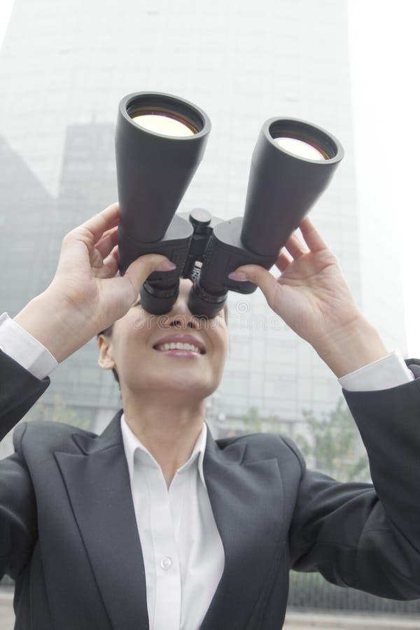 Uśmiechnięty bizneswoman w kostiumu przyglądającym przez lornetek w Pekin up outdoors obrazy stock
