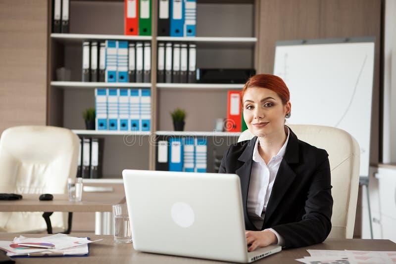 Uśmiechnięty bizneswoman z laptopem przed jej patrzeć kamerę zdjęcia stock