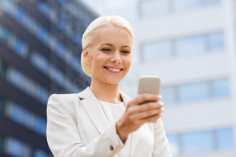 Uśmiechnięty bizneswoman z smartphone outdoors obrazy royalty free