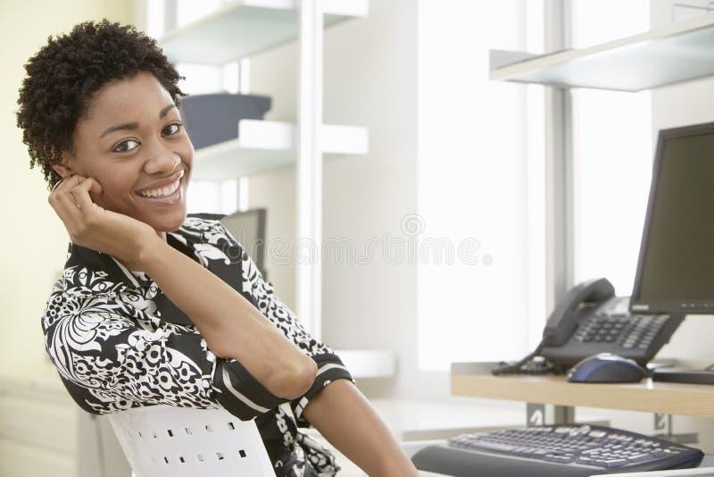 Uśmiechnięty bizneswomanu obsiadanie Przy Komputerowym biurkiem obrazy royalty free