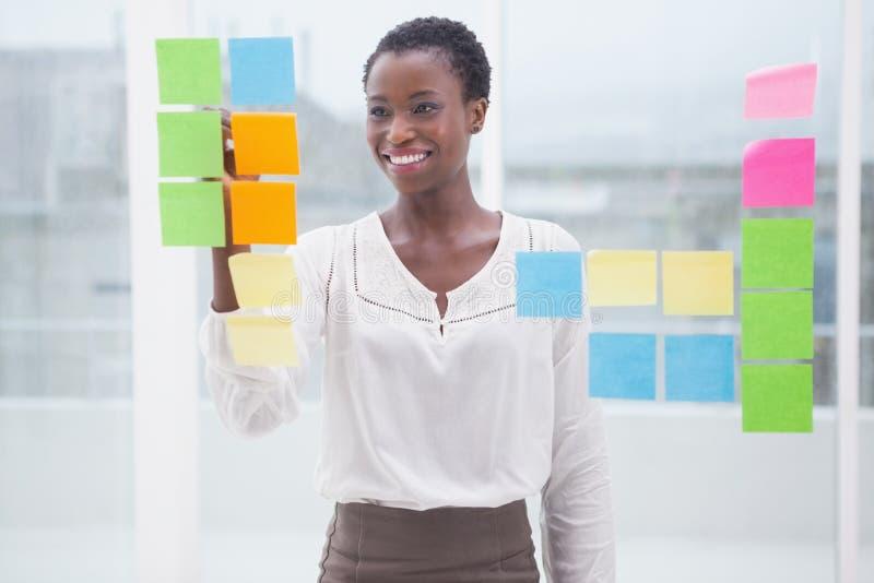 Uśmiechnięty bizneswomanu writing na kleistych notatkach na okno obraz stock