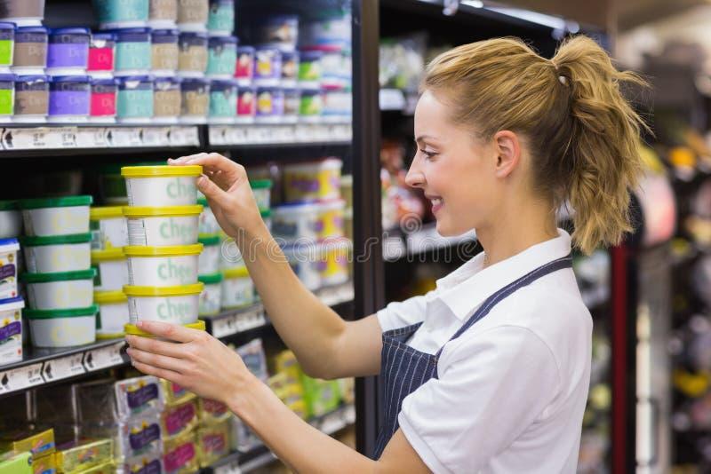 Uśmiechnięty blondynka pracownika brać produkty w półce fotografia stock