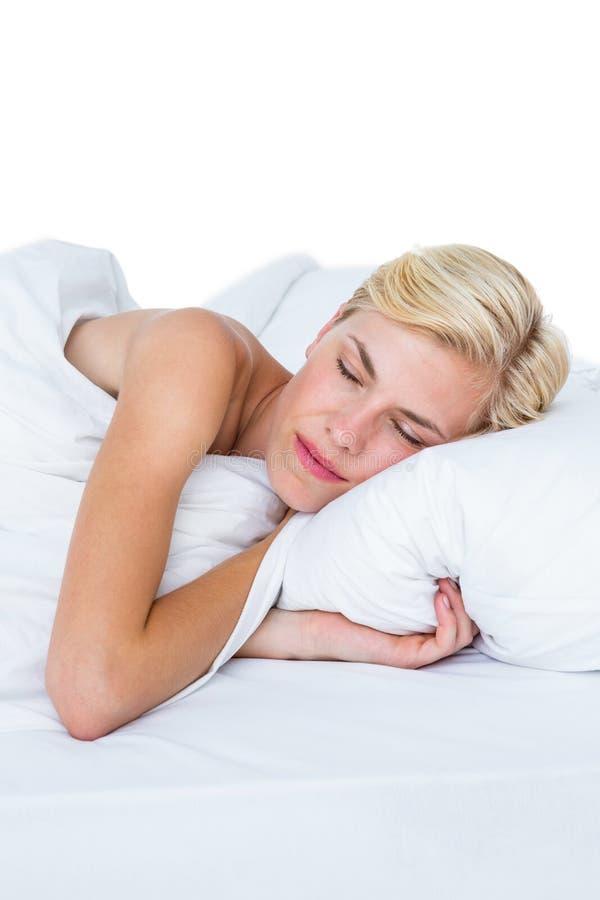 Uśmiechnięty blondynki kobiety drzemanie w jej łóżku obrazy stock