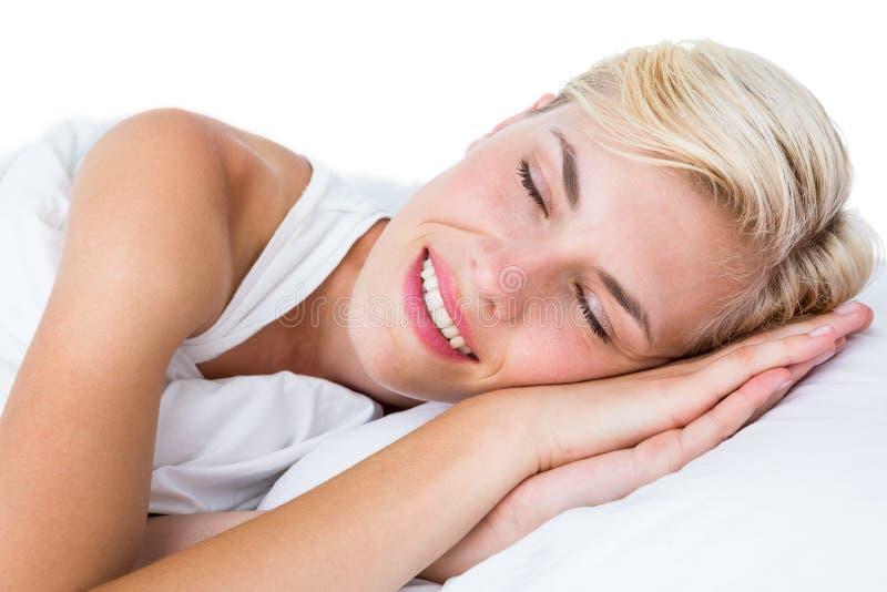 Uśmiechnięty blondynki kobiety drzemanie w jej łóżku obraz stock