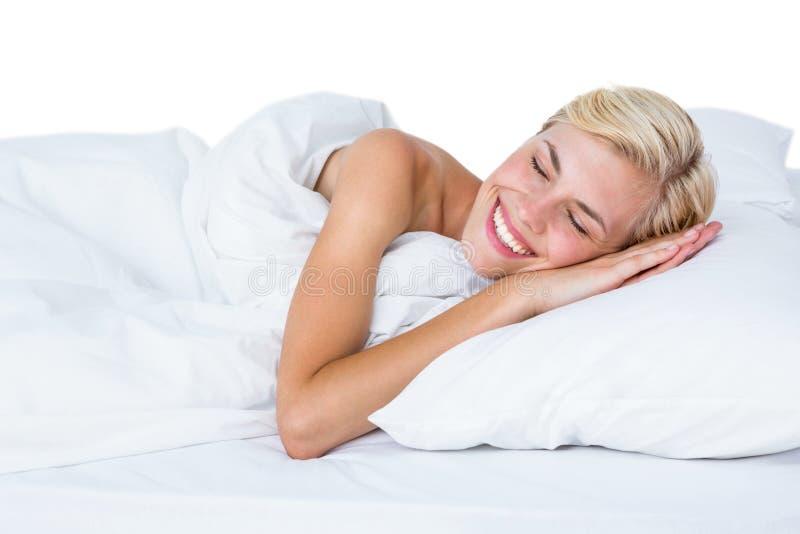 Uśmiechnięty blondynki kobiety drzemanie w jej łóżku zdjęcia stock