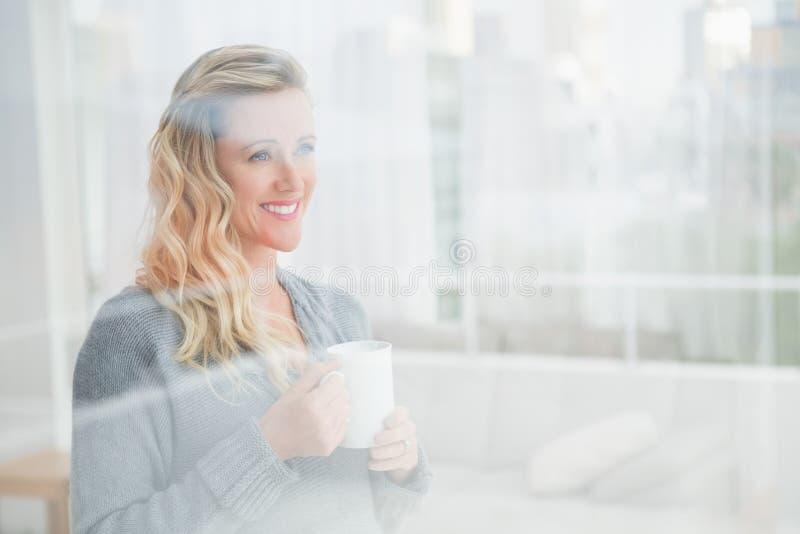 Uśmiechnięty blondynki kobiety mienia kubek kawowy patrzeć daleko od zdjęcia royalty free