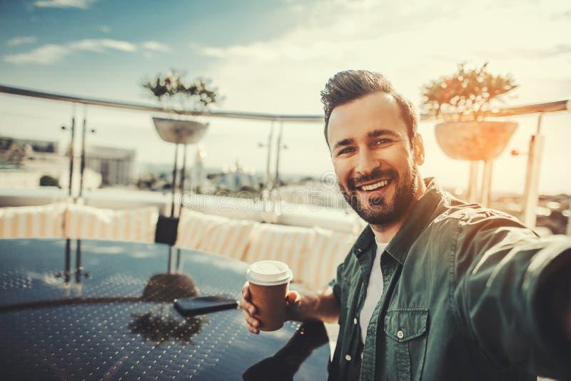 Uśmiechnięty brodaty mężczyzna robi selfie podczas kawowej przerwy zdjęcie stock