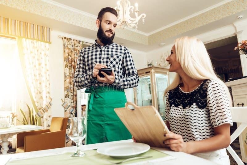 Uśmiechnięty brodaty młody kelner bierze rozkaz w kawiarni obraz stock