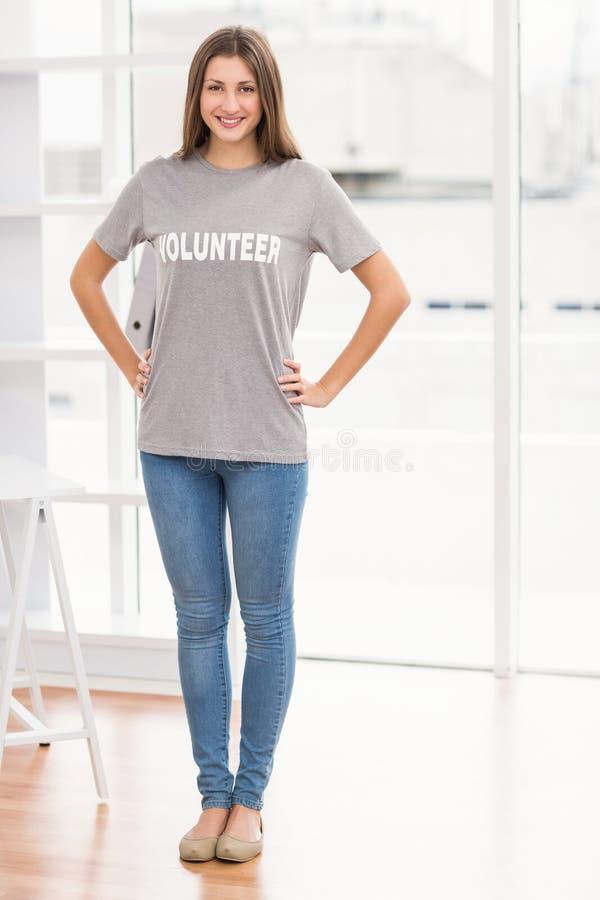 Uśmiechnięty brunetka wolontariusz z rękami na biodrach zdjęcie stock