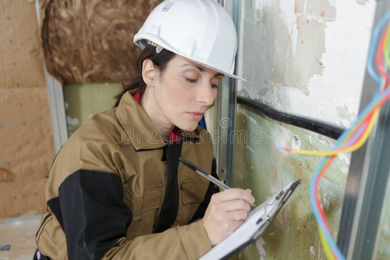 Uśmiechnięty budowa żeńskiego pracownika mienia schowek obraz royalty free