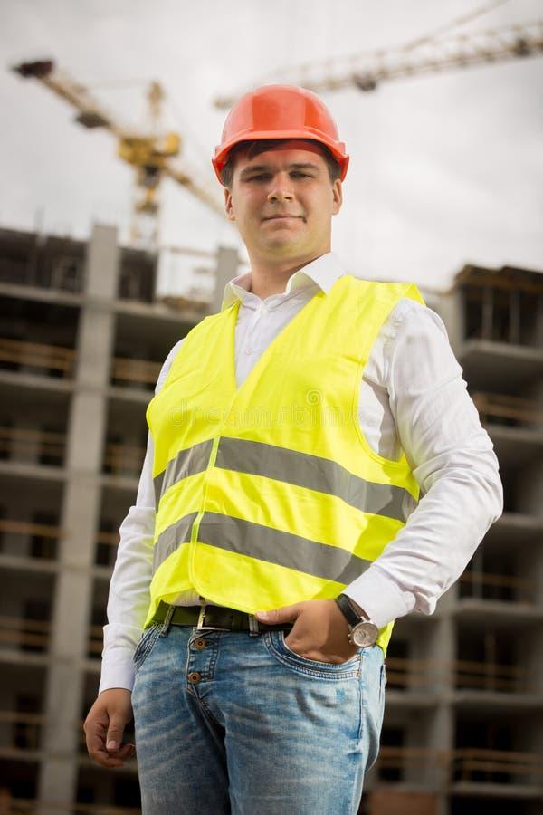 Uśmiechnięty budowa inżynier patrzeje kamerę w hardhat zdjęcie royalty free