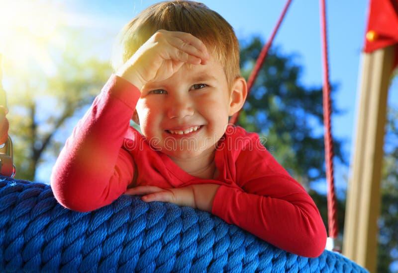 Uśmiechnięty chłopiec chlanie na huśtawce zdjęcie stock