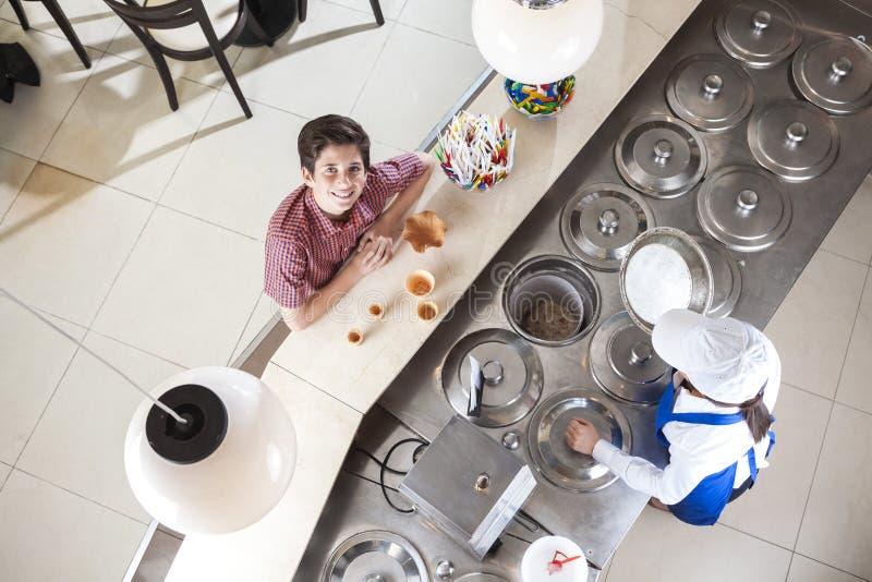 Uśmiechnięty chłopiec kupienia lody Od kelnerki Przy kontuarem obraz royalty free