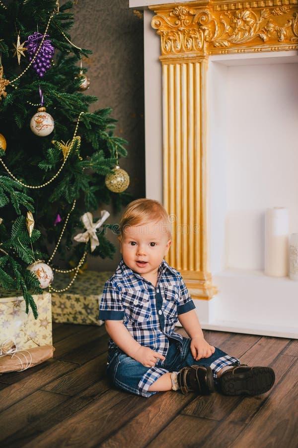 Uśmiechnięty chłopiec obsiadanie pod Chritmas drzewną pobliską grabą zdjęcia stock