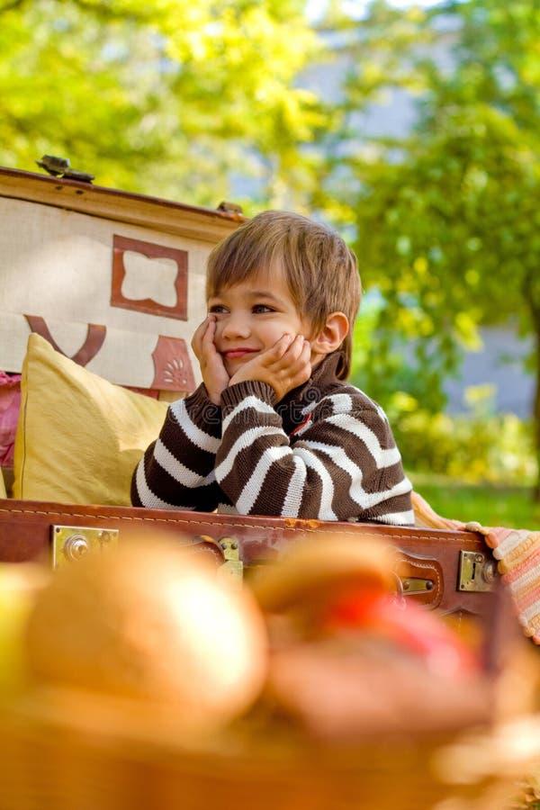 Uśmiechnięty chłopiec obsiadanie w walizce zdjęcie royalty free