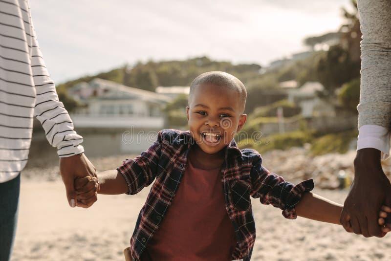 Uśmiechnięty chłopiec odprowadzenie z rodzicami na plaży obraz royalty free