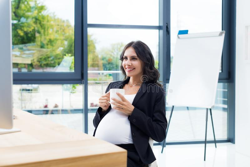 uśmiechnięty ciężarny bizneswoman z filiżanką gorący napój fotografia stock