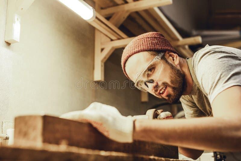 Uśmiechnięty cieśla pracuje z drewnianą deską fotografia stock