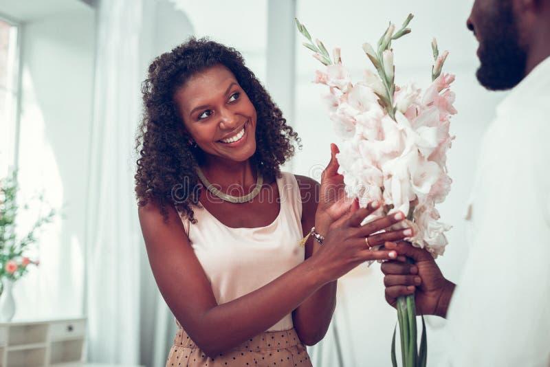 Uśmiechnięty ciemnowłosy amerykanin kobiety dostawanie kwitnie od męża obraz royalty free