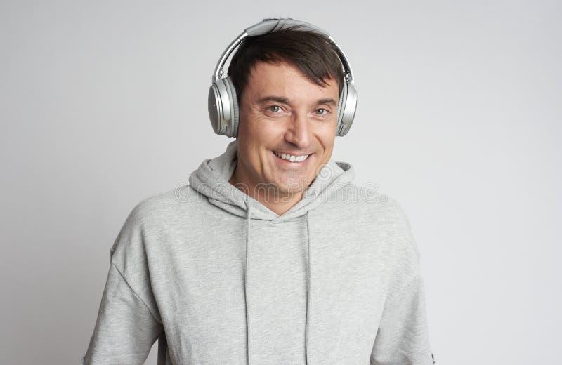 Uśmiechnięty człowiek słuchający muzyki w odizolowanych słuchawkach obraz royalty free