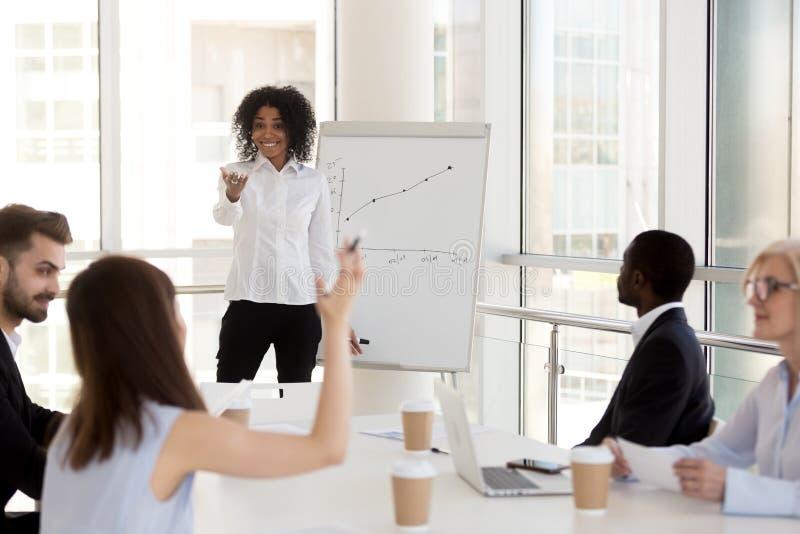 Uśmiechnięty czarny żeński mentor oddziała wzajemnie z pracownikami podczas pr zdjęcia stock