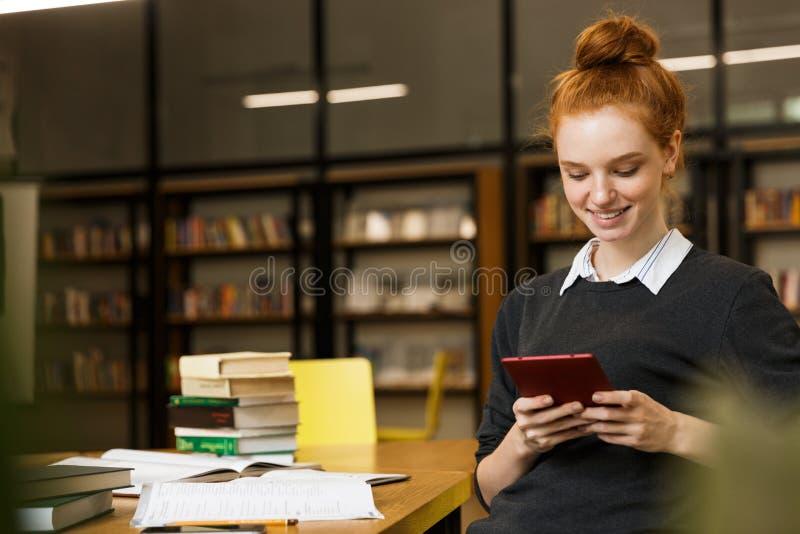 Uśmiechnięty czerwony z włosami nastoletniej dziewczyny studiowanie obrazy royalty free